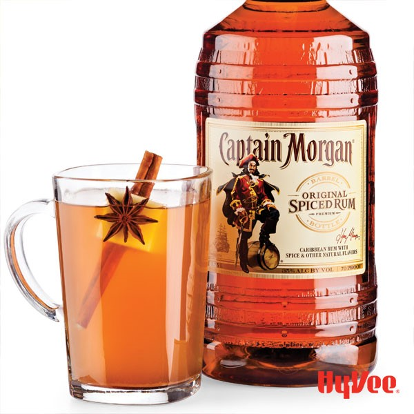 Glass of Captain Morgan spiced cider garnished with star anise, apple wedge and cinnamon stick