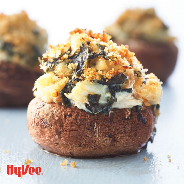 Baby bella mushroom filled with crabmeat and spinach dip, garnished with bread crumbs and Parmesan cheese