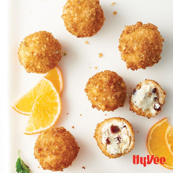 Breaded creamy goat cheese balls with dried cranberries and orange slices on the side