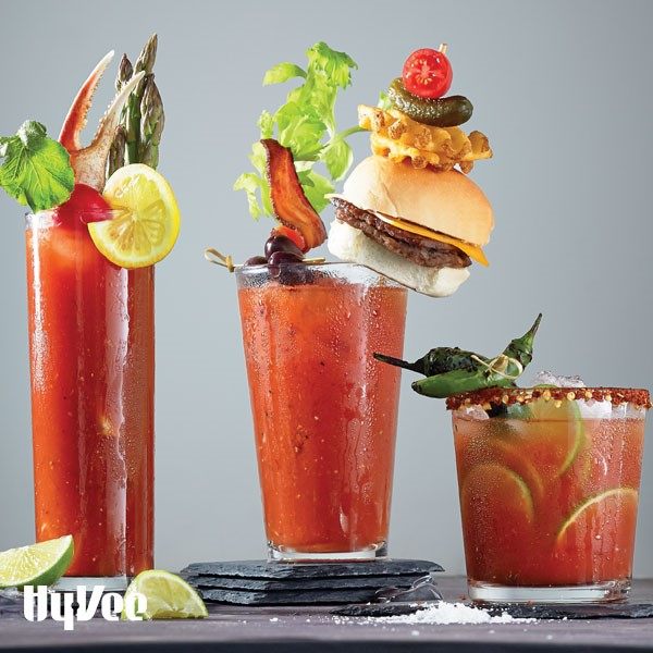 Three glasses filled with bloody marys and topped with crab claws, mini burgers, hot peppers, olives, and bacon