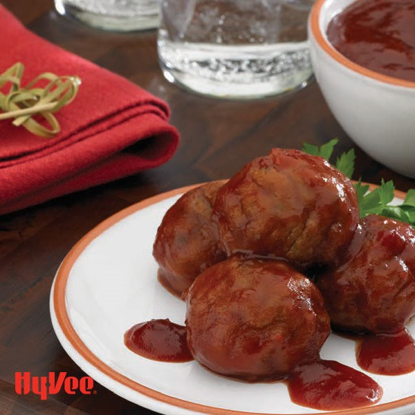 Meatballs covered in sauce and garnished with fresh parsley