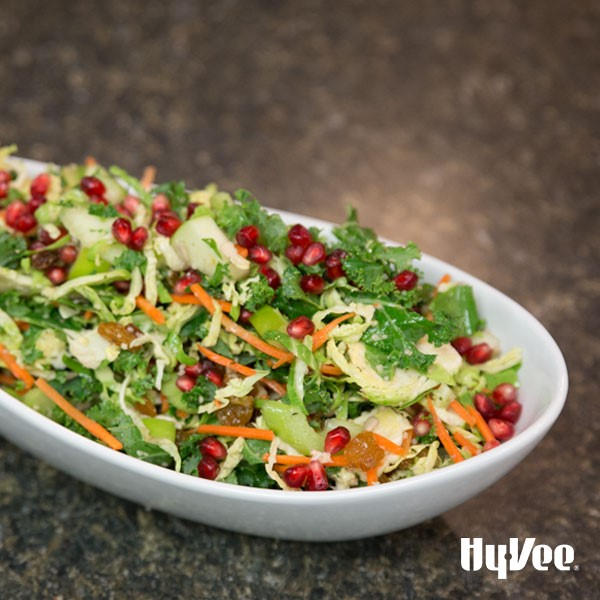 White serving dish topped with brussels sprouts, pomegranate seeds, and shredded carrots