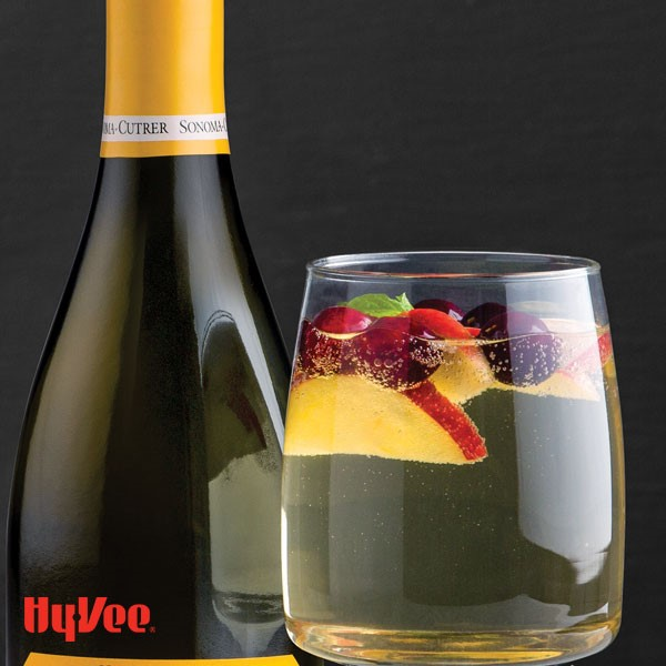 Glass of sparkling apple chardonnay, garnished with apple slices, berries and mint