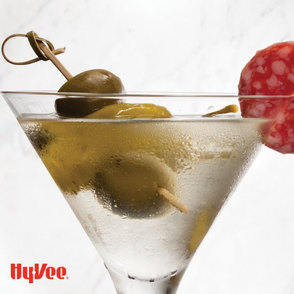 Martini in a martini glass with whole olives and pepperoni slice on rim