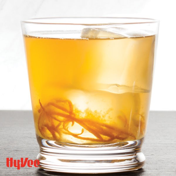 Glass with whisky, ice cube, and orange zest