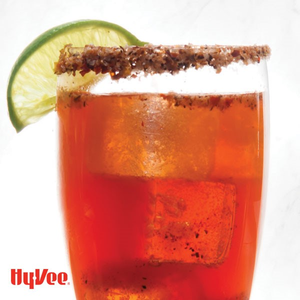 Glass filled with ice, red beverage, with a spice laced rim and lime wedge for garnish