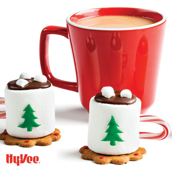 Large marshmallows on cookies with candy cane handles, green fondant Christmas tree cut out and red mug of cocoa on side