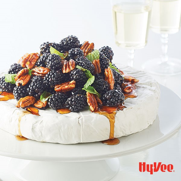 Brie cheese wheel topped with black berries, pecans, mint leaves, and syrup