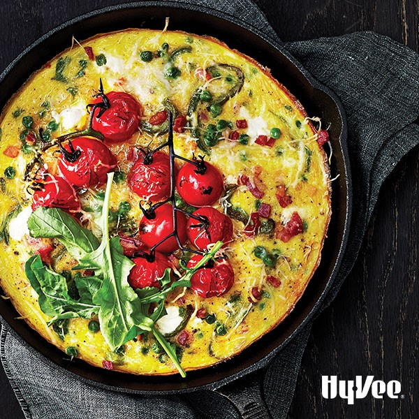 Cast iron skillet filled with an egg frittata, tomatoes on the vine, and fresh arugula