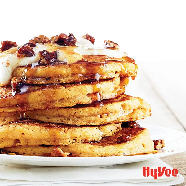 Pancakes topped with pecans, maple whipped cream and pecans