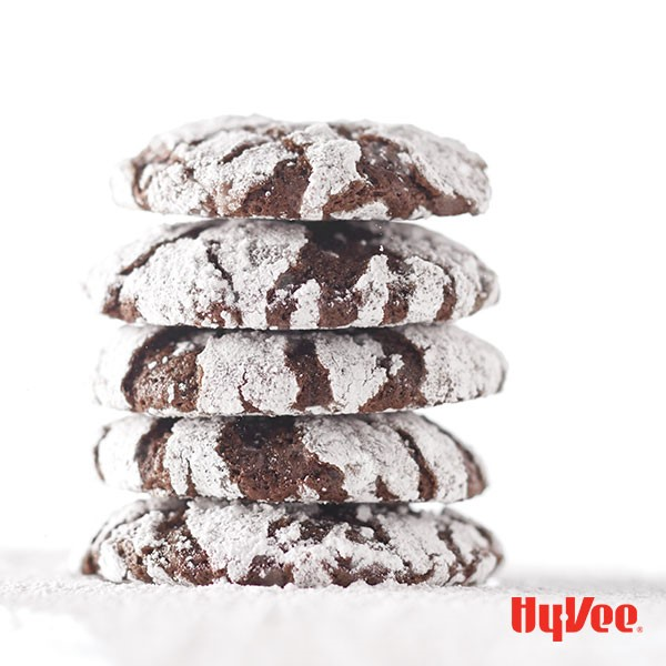 Stacked chocolate crinkle cookies covered in powdered sugar