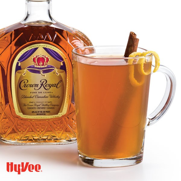 Mug filled with Hot Toddy , cinnamon stick, and lemon peel with Crown Royal bottle in background