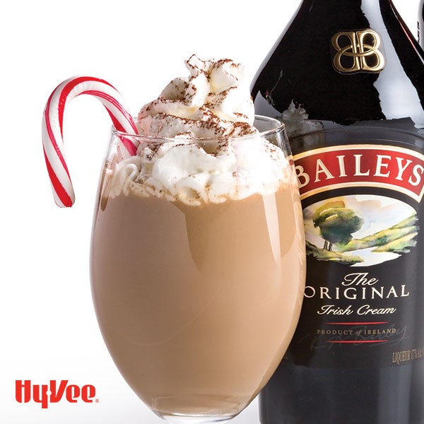 Wine glass filled with coffee, whipped cream, and candy cane next to a bottle of Irish Cream
