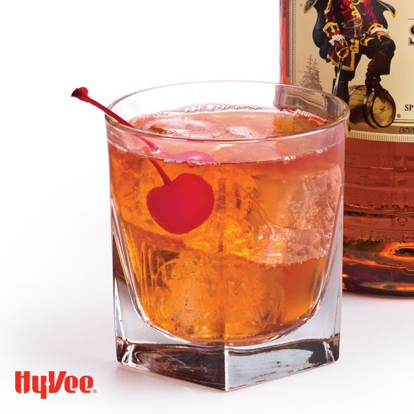 Glass of cherry and Captain garnished with a maraschino cherry