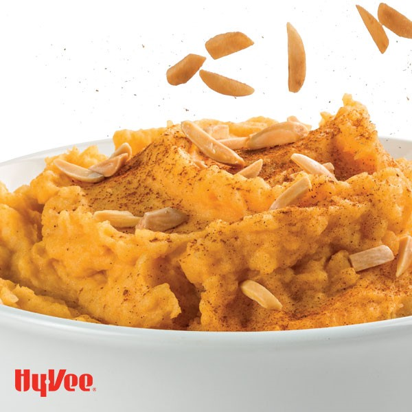 Bowl of mashed sweet potatoes, garnished with almonds and cinnamon