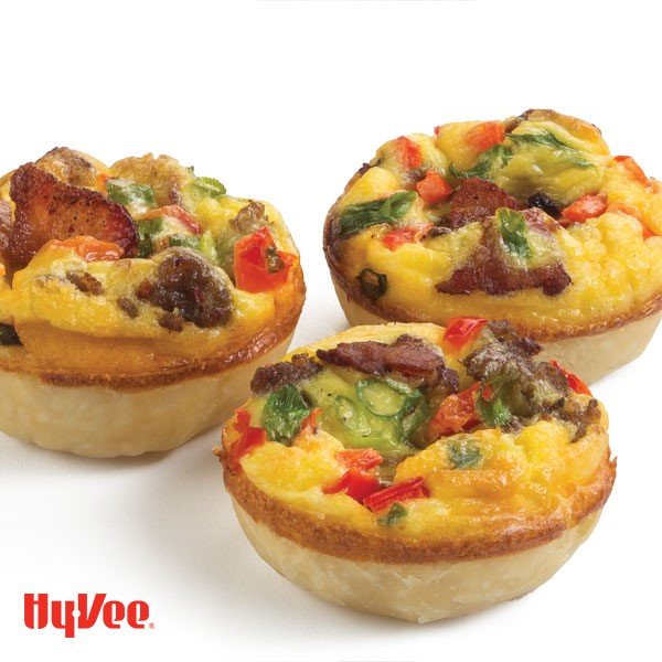 Small quiches topped with bacon slices, cheese, peppers, and sliced green onion