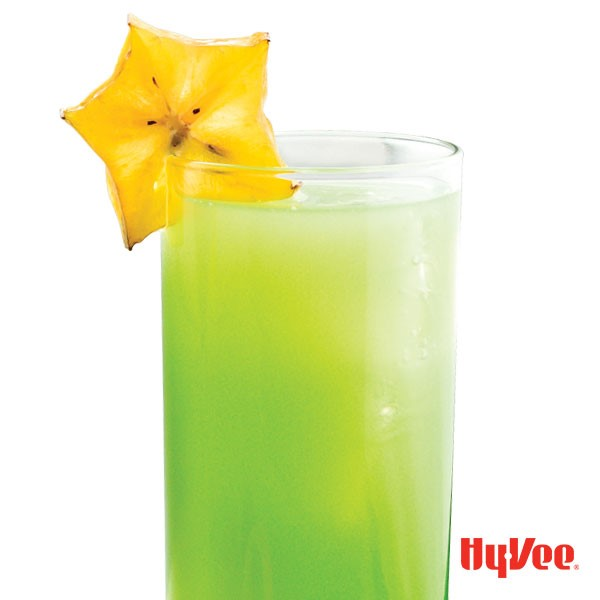 Glass of lime-green starfruit vodka fizz, garnished with a starfruit