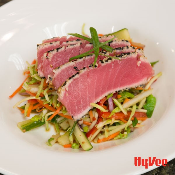 Asian slaw topped with sesame encrusted tuna steaks, served in a bowl
