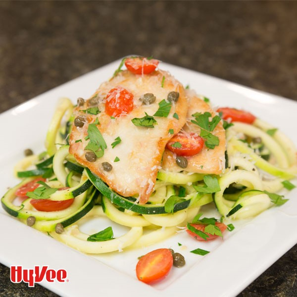 Plate of chicken piccata over zucchini noodles and cherry tomatoes