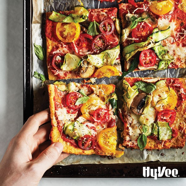 Tray of cauliflower crust pizza topped with cheese and vegetables