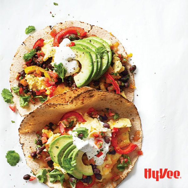 Whole wheat soft-shell tortillas filled with scrambled egg, pico de gallo, black beans, cilantro, bell peppers, cheese, avocado and a dollop of greek yogurt