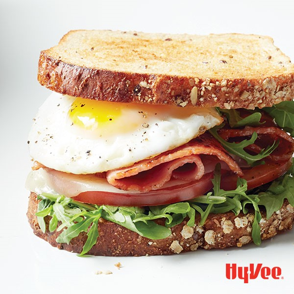 Sandwich filled with arugula, tomato slices, melted cheese, bacon, and a fried egg