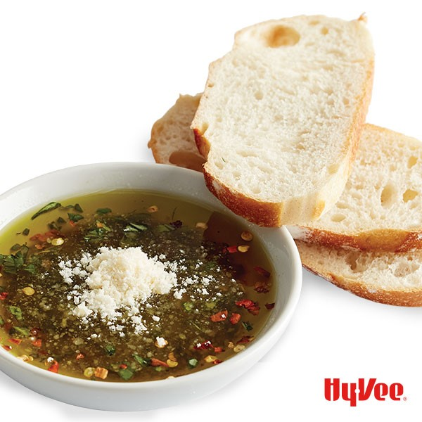 Stacked bread slices next to white bowl filled with olive oil, balsamic, red pepper flakes, grated Parmesan cheese, and sliced basil