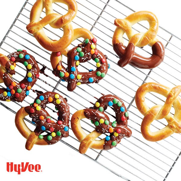 Soft pretzels dipped in melted chocolate and M&M's on a wire rack