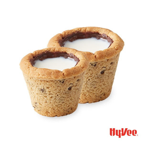 Chocolate chip cookie in muffin cups with hole in middle coated with melted chocolate and filled with milk
