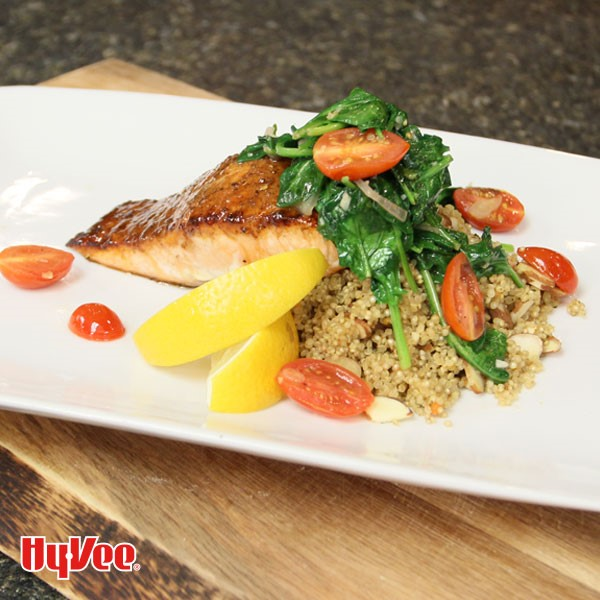 Plate of salmon topped with spinach and tomatoes over a bed of quinoa and garnished with lemon wedges