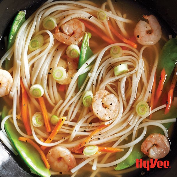 Pot of soup broth mixed with thin rice noodles, shredded carrots, shrimp, snow peas and green onions