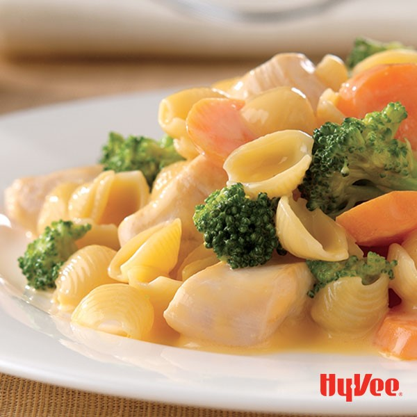 Velveeta cheese shells, diced chicken, broccoli, and carrots on a plate drizzled with cheese sauce