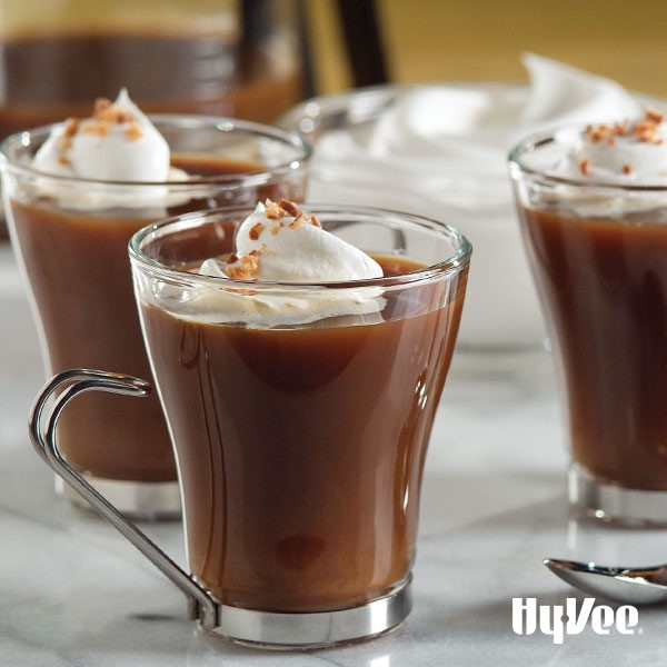 Glass mug of caramel coffee topped with whipped topping and chopped chocolate-covered toffee bar