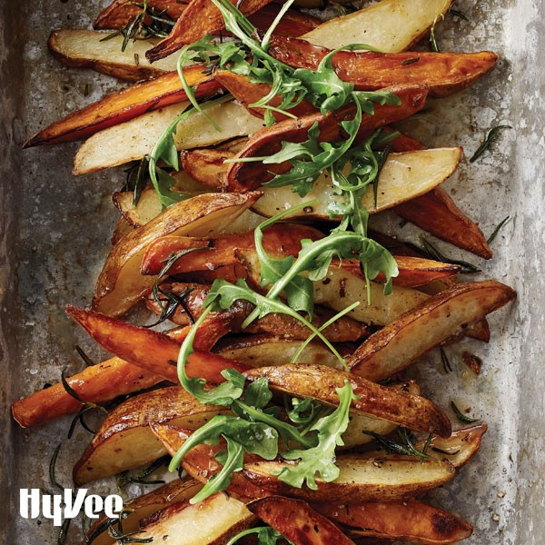 Roasted potato wedges on metal sheet pan topped with fresh rosemary and fresh arugula