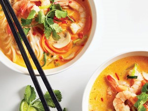 Orange broth filled with rice noodles, shredded carrots, sliced mushrooms, and tail-on cooked shrimp garnished with fresh cilantro