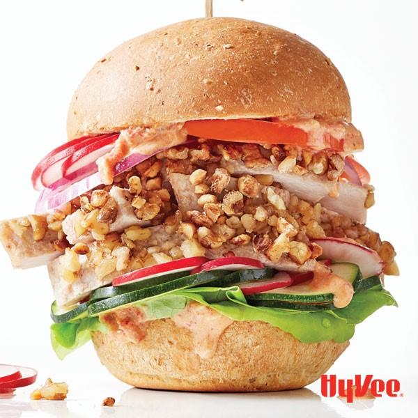 Walnut-encrusted turkey tenderloin in between hamburger bun with sandwich spread, lettuce, tomato, onion, zucchini and radish