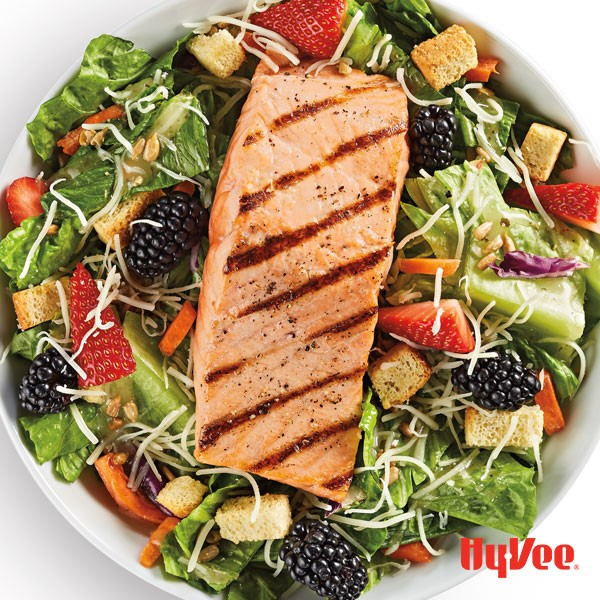 A salmon fillet over a bed of lettuce, garnished with fresh strawberries and blackberries