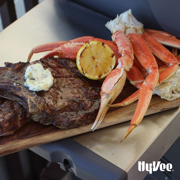 Grilled steak with compound butter next to grilled crab legs garnished with grilled lemon half