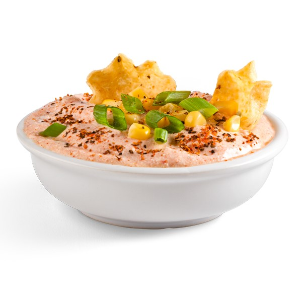 White bowl filled with orange dip and topped with chopped green onions, corn kernels, and tortilla chips