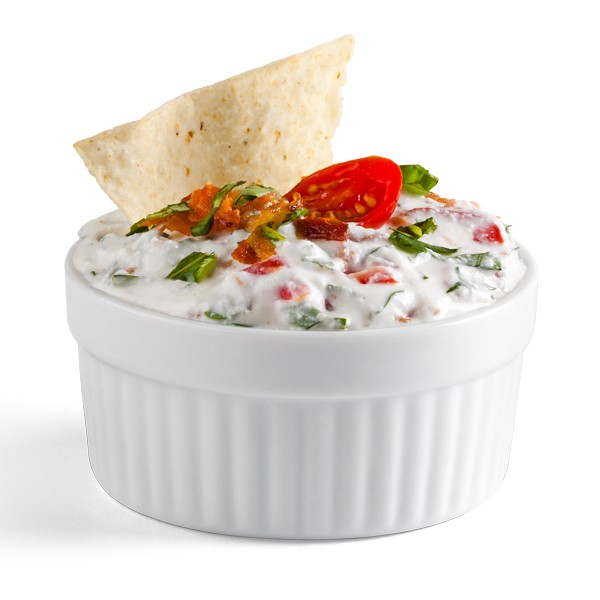 Ramekin filled with bacon, basil, and tomato dip with flour tortilla chip for garnish