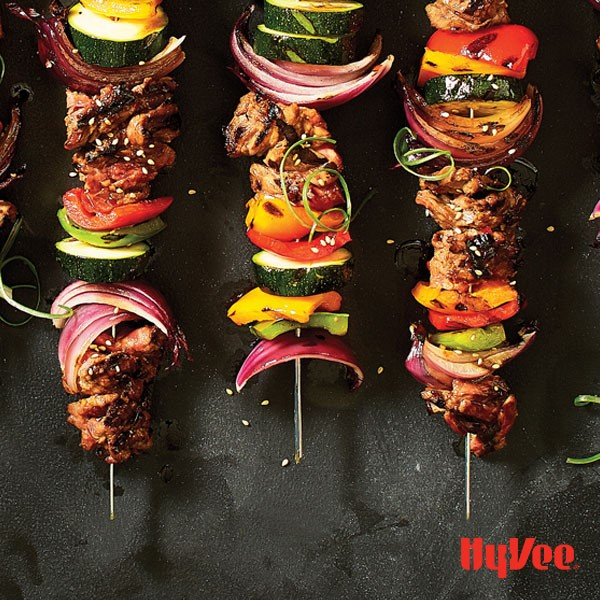 Skewers of beef, red onion, multi colored peppers, and zucchini on metal skewers sprinkled with sesame seeds