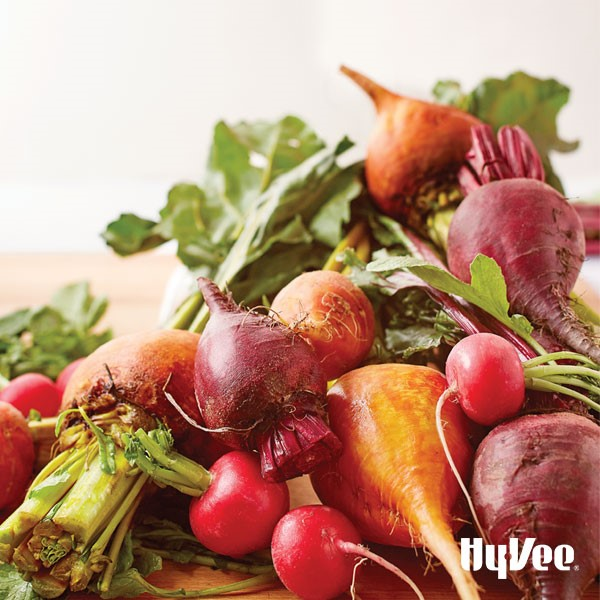 Raw red and yellow beets with raw radishes with tops on a wooden cutting board