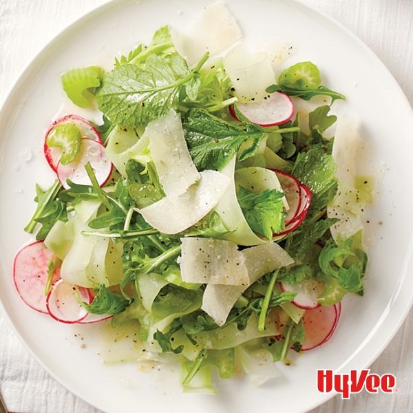 White plate topped with mixed greens, thinly sliced radishes, and shaved Parmesan cheese