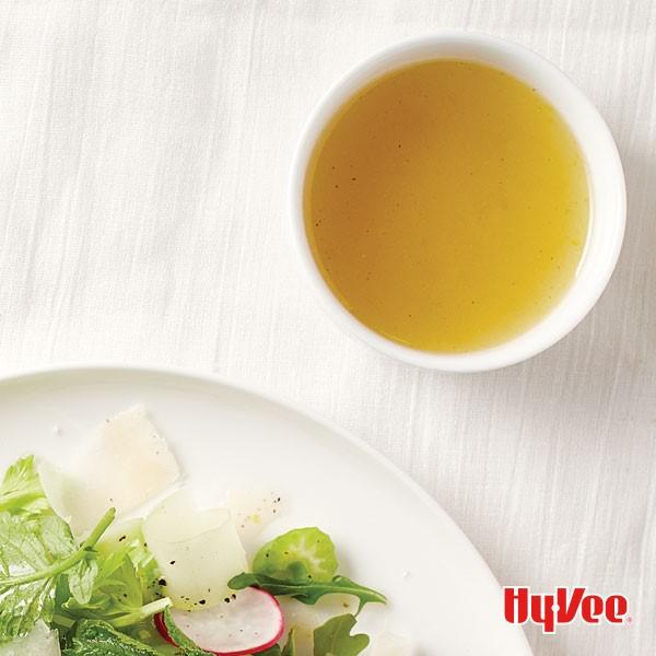Lemon-honey vinaigrette in a small bowl next to a leafy green salad