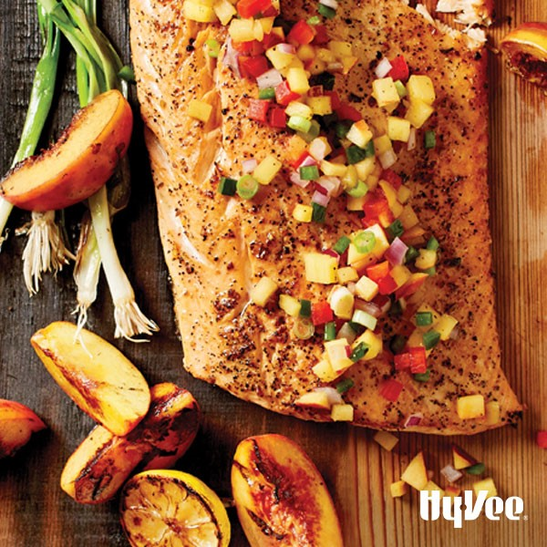 Salmon topped with peach salsa on a wooden plank