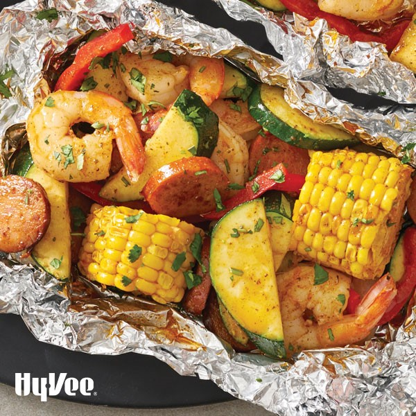 Aluminum foil wrap filled with boiled corn, shrimp, sausage and squash