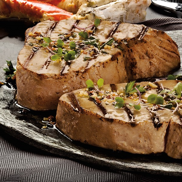 Grilled tuna steaks with garlic olive oil and garnished with fresh oregano and parsley