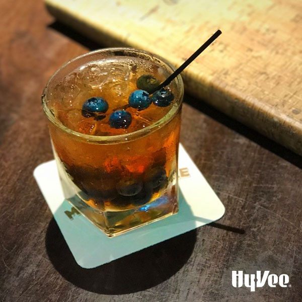 Drink in a glass topped with ice, whole blueberries, and black straw