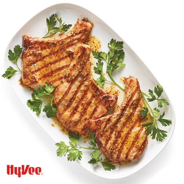 Bone-in pork chops topped with mustard sauce and garnished with Italian parsley