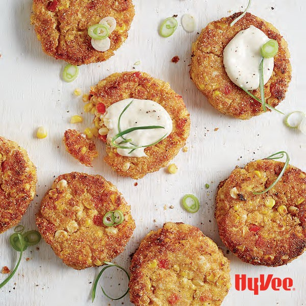 Fried corn cakes topped with aioli, and chopped green onions